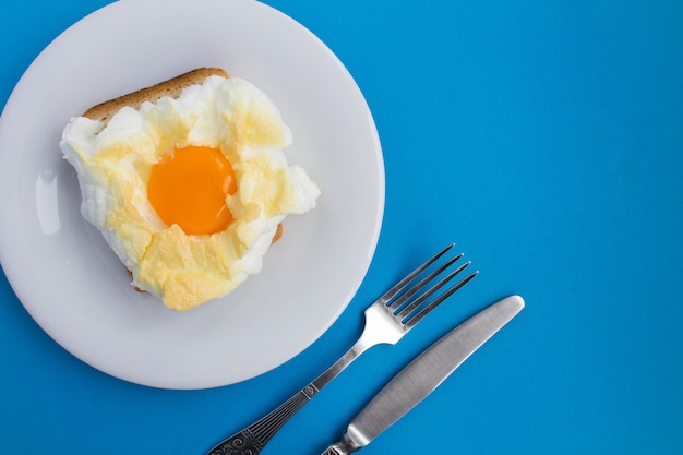 青い背景の白いプレートの雲の中に卵とサンドイッチ。上面図。コピースペース。