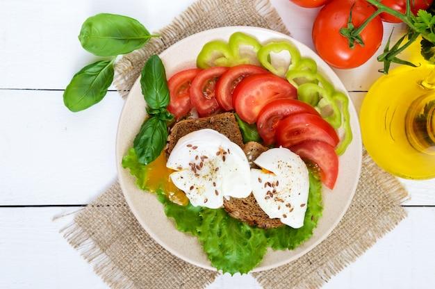 卵のポーチ、レタス、黒パン、種子、トマト、ピーマン、白い木製のテーブルプレートのサンドイッチ。トップビュー
