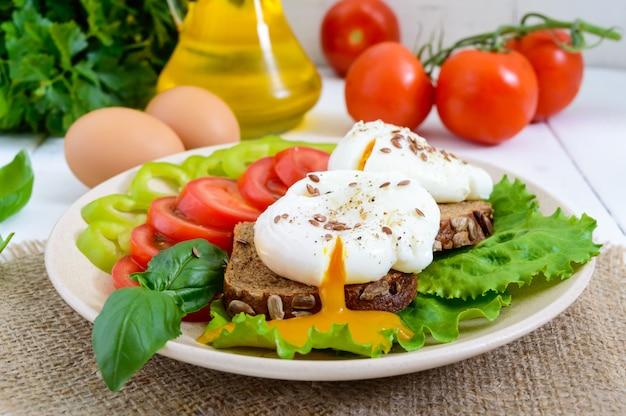 卵のポーチ、レタス、黒パン、種子、トマト、ピーマン、白い木製のテーブルプレートのサンドイッチ。