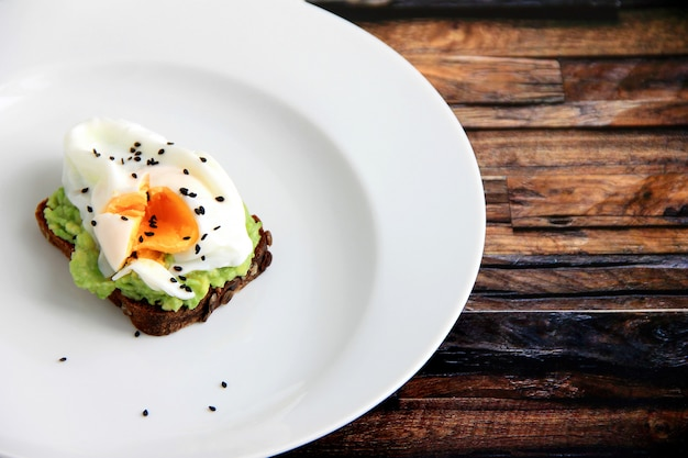 Sandwich with egg in a white plate on a wooden background