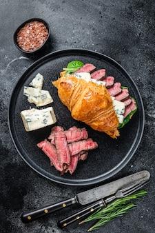 필레 미뇽 고기 스테이크, 크루아상 및 블루 치즈 샌드위치. 검정색 배경. 평면도.