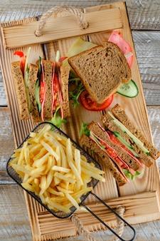 木製トレイのフライドポテトトップビューのサンドイッチ