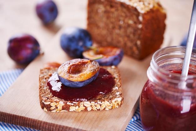 Sandwich with fresh plum jam on cutting board