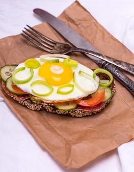 A sandwich with fried egg and a piece of rye bread