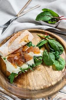 Сэндвич с козьим сыром, грушевым мармеладом, мангольдом и шпинатом на хлебе багет. белый деревянный фон. вид сверху.