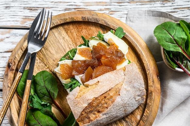 Сэндвич с козьим сыром, грушевым мармеладом, мангольдом и шпинатом на хлебе багет. ,