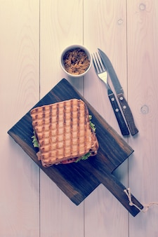 Sandwich with grilled bread with french dijon mustard on a wooden board