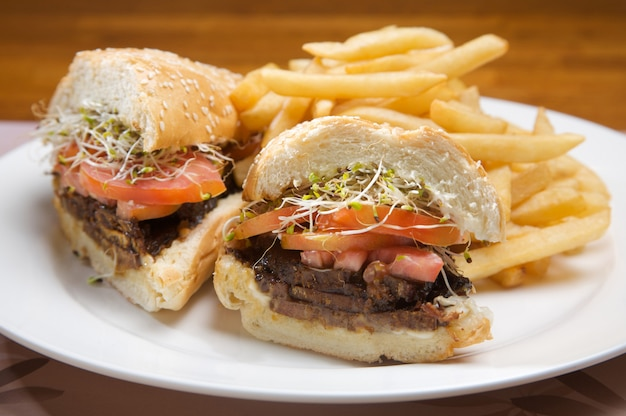 Sandwich with grilled veal with sauce and tomato. accompanied by french fries