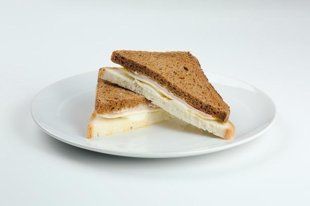 고립 된 하얀 접시에 햄과 치즈 샌드위치. 다른 빵 근접 촬영과 클럽 샌드위치