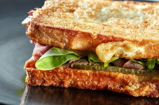 黒いプレートにハムとグリーンサラダグリルのサンドイッチ