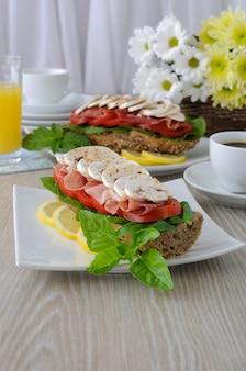 커피와 주스 한 잔과 함께 햄과 버섯 샌드위치
