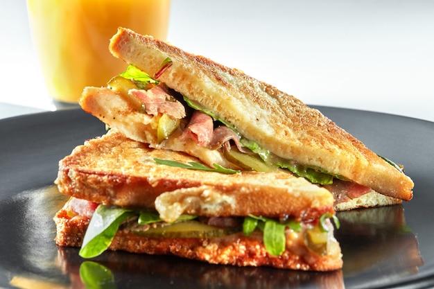黒いプレートにハムとオレンジジュースのグリルが付いたサンドイッチ