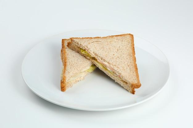 햄과 샐러드와 통곡물을 곁들인 샌드위치는 하얀 접시에 구운 빵입니다. 고립된 클럽 샌드위치