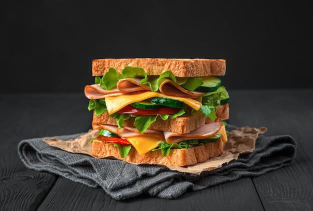 검은색 바탕에 햄 치즈와 신선한 야채를 넣은 샌드위치
