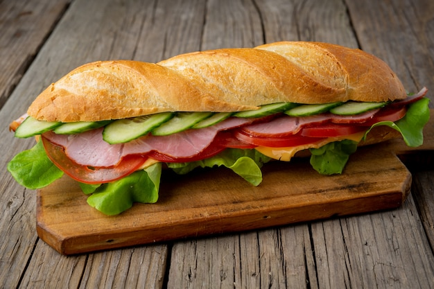 Sandwich with ham, cheese, tomatoes, cucumbers, lettuce on dark wooden background