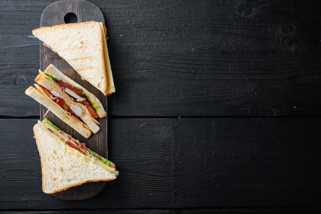ハム、チーズ、トマト、レタス、鶏肉、トーストしたパンのサンドイッチ、黒い木製のテーブル、テキストのコピースペースのある上面図