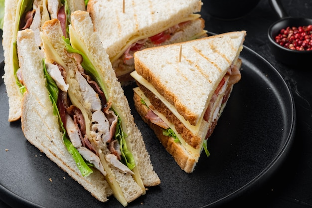 Sandwich with ham, cheese, tomatoes, lettuce, chicken meat and toasted bread, on black background