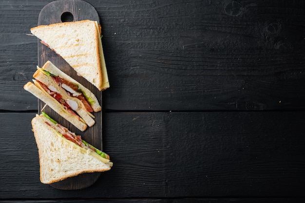Sandwich with ham, cheese, tomatoes, lettuce, chicken meat and toasted bread, on black wooden table, top view with copy space for text