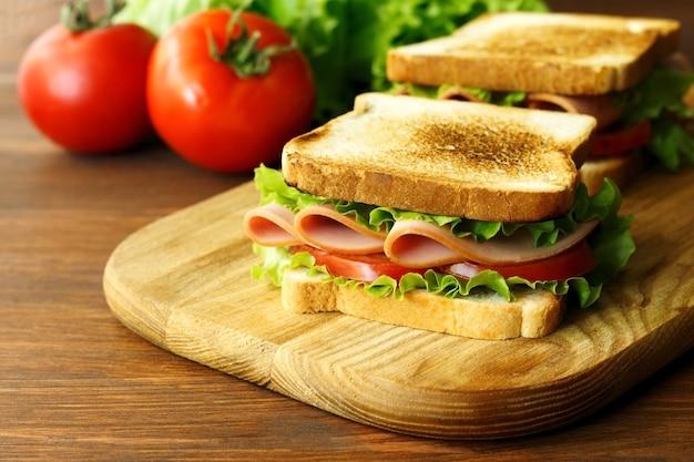 나무 갈색 부엌 보드에 햄 녹색 양상추와 토마토 샌드위치