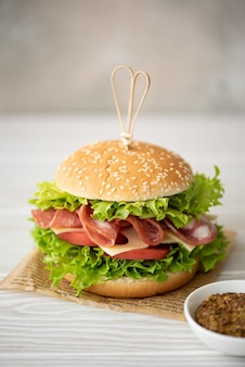 Sandwich with ham, maasdam cheese, tomatoes and green salad on a white table