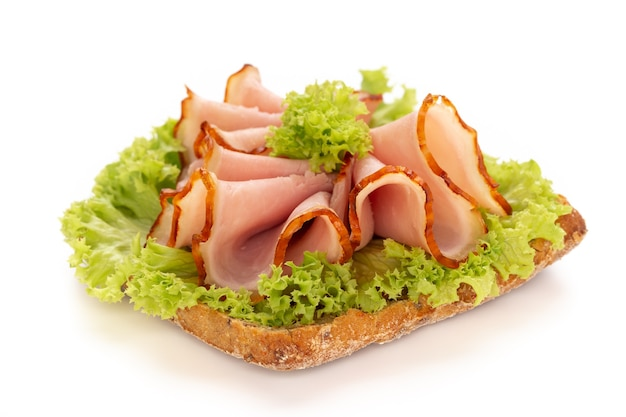 Sandwich with ham sausage on white surface.