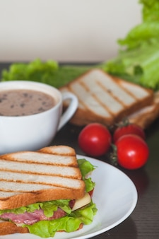 Sandwich with ham; spinach leaf and cheese on white plate with coffee