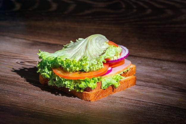 Бутерброд с ветчиной, помидорами и зеленым салатом на темном столе.