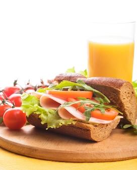 Бутерброд с ветчиной, помидорами, решеткой и рукколой со стаканом апельсинового сока с копией пространства.