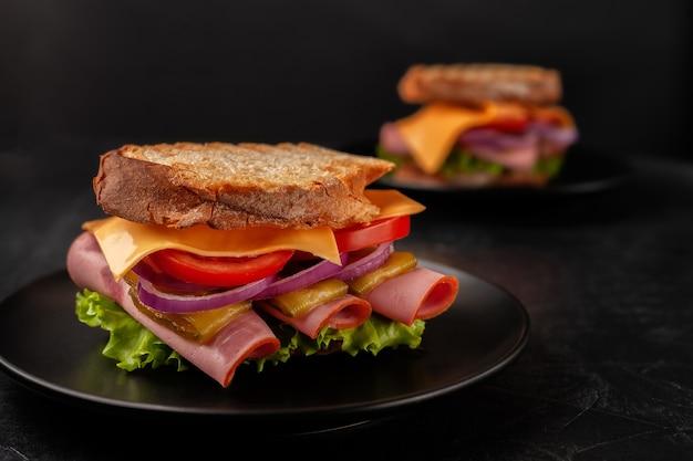 햄, 토마토, 양상추와 검은 색에 노란색 치즈 샌드위치