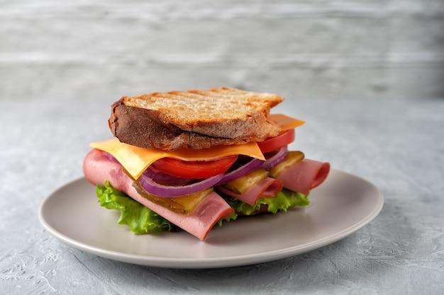 햄, 토마토, 양상추, 회색 배경에 노란색 치즈 샌드위치