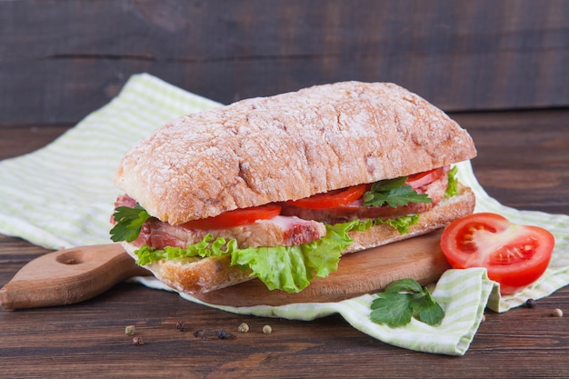 Sandwich with ham and vegetables on a dark wooden background.