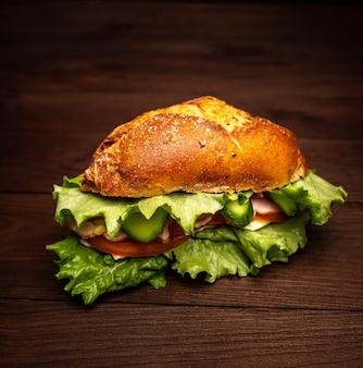 Бутерброд с зеленью, сыром, помидорами и беконом на деревянном столе