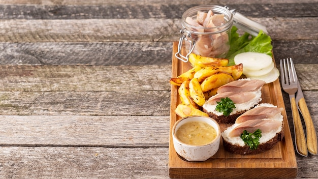 Бутерброд с селедкой и печеным картофелем на деревянной доске.