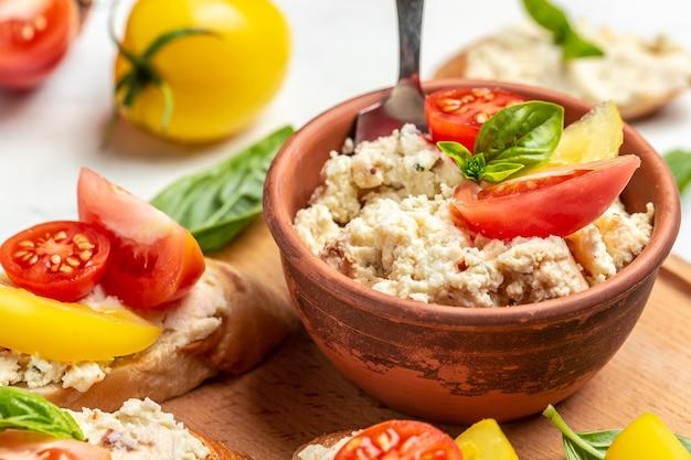Сэндвич с домашним творогом, помидорами черри и базиликом. вкусный завтрак или закуска, чистое питание, диета, концепция веганского питания. вид сверху.