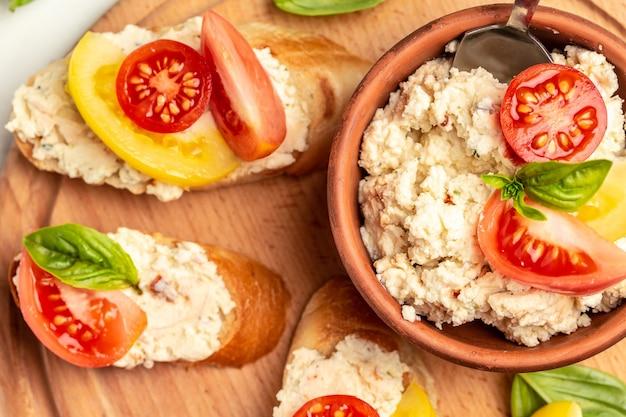 Бутерброд с домашним творогом, помидорами черри и базиликом на деревянной доске. тенденция здорового питания