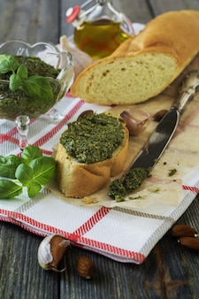 Sandwich with homemade pesto ,basil, olive oil, and garlic on an old wooden table