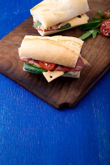 Sandwich with jamon, arugula, tomatoes, cheese on wooden board blue surface