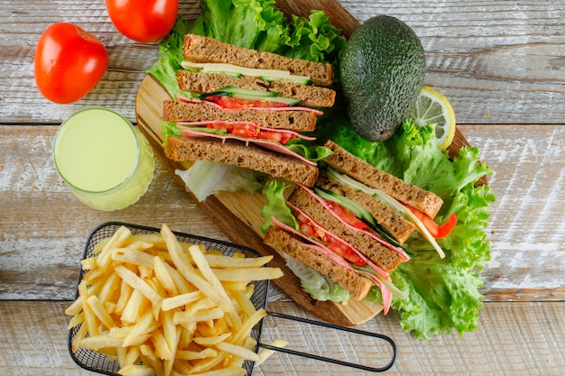 Sandwich with lemonade, avocado, french fries, tomatoes flat lay on wooden and cutting board