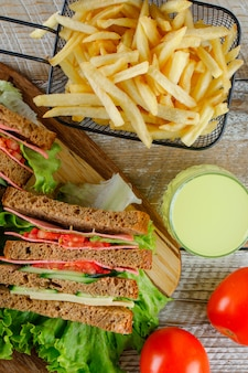 Sandwich with lemonade, french fries, tomatoes flat lay on wooden and cutting board