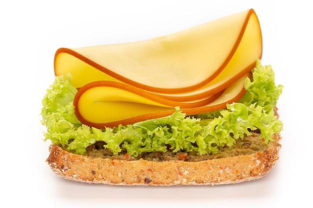 Сэндвич с листьями салата, сыром на белой поверхности.