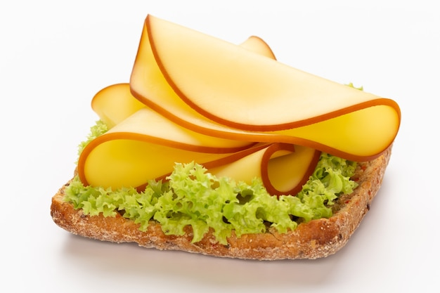 Sandwich with lettuce, cheese on white surface.