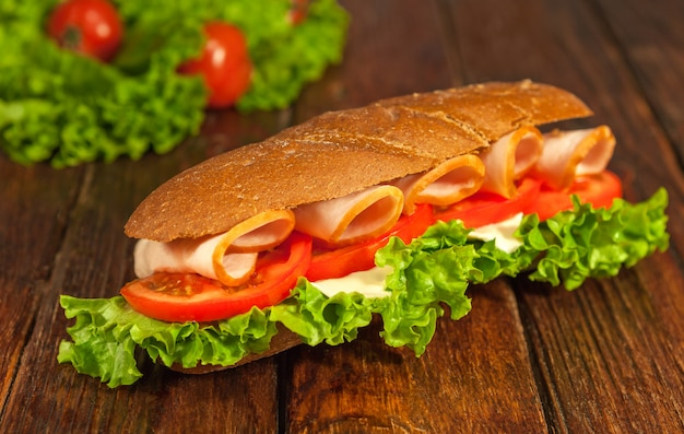 Sandwich with lettuce, tomatoes, ham, and cheese on wooden table.