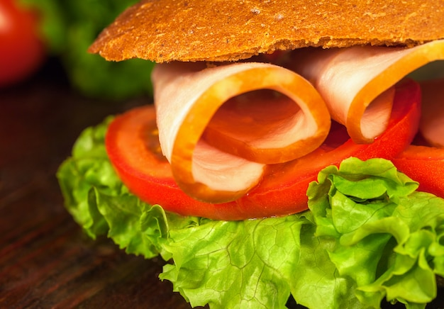 Sandwich with lettuce, tomatoes, ham, on wooden table. closeup