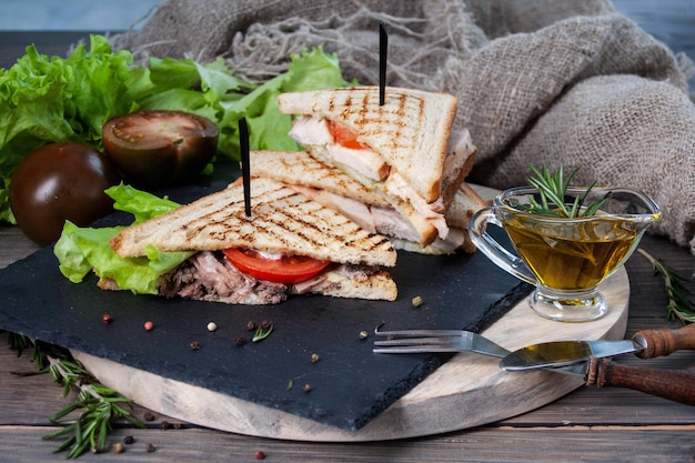 Sandwich with meat and fresh vegetables on a wooden table