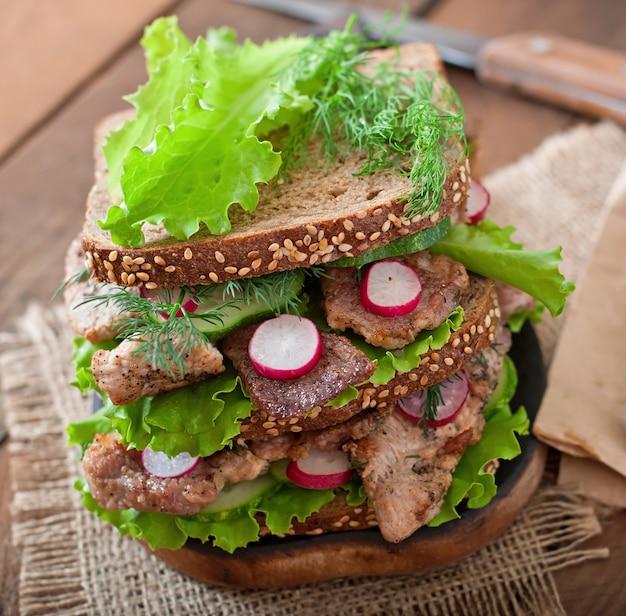 Бутерброд с мясом, овощами и ломтиками ржаного хлеба