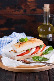 Sandwich with mozzarella and basil on a table