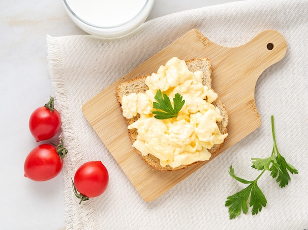 Sandwich with pan-fried scrambled eggs on wooden cutting board, top view.