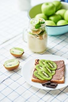 ピーナッツバターとキウイのサンドイッチ、青リンゴ、バナナとキウイのヨーグルト、子供の朝食、デザート、休日の食事のための独創的なアイデア、平面図、子供のための健康食品。おはようございます