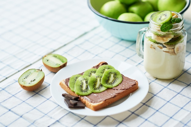 Sandwich with peanut butter and kiwi, green apples, yogurt with banana and kiwi, creative idea for kids breakfast, dessert or holiday meal, top view flat lay, healthy food for children. good morning