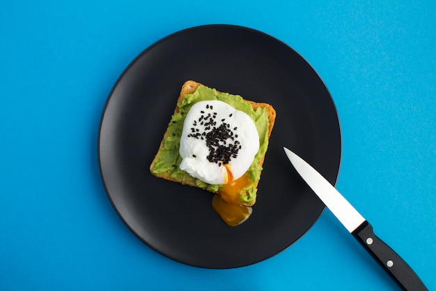 Sandwich with poached egg and avocado on the black plate in the center of the blue background